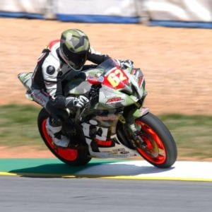 MotoAmerica racer riding on our painted race track apron